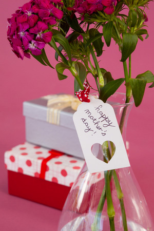 Close-up of happy mothers day card on flowers vase against pink background