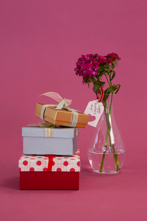 Stack Of Gift Boxes And Flowers Vase On Pink Background Stock Photo