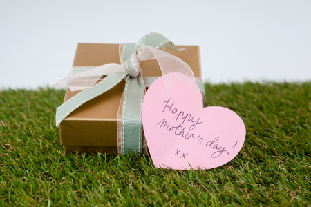 Happy mothers day card on gift box against white background