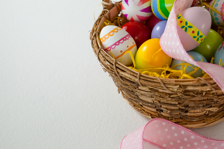 Various Easter eggs with ribbon in wicker basket on white background Stock Photo
