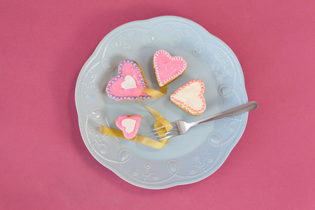 Decorated heart shape gingerbread cookies and fork kept on plate