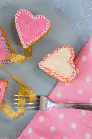 Close-up of heart shape gingerbread cookies and fork kept on plate