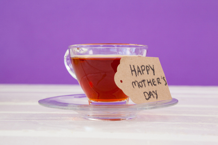 Happy mothers day card with cup of herbal tea on white table