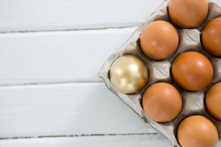 concern: Close-up of golden Easter egg with brown eggs in tray