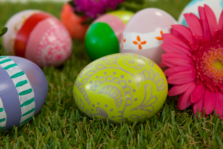 Painted easter eggs with pink flower on grass