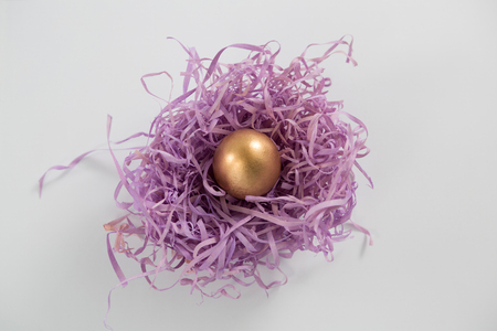 Close-up of golden Easter eggs in the paper nest on white background