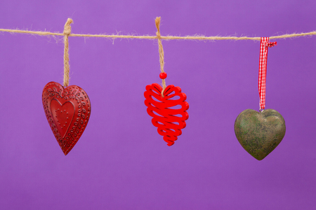 Hearts with different designs hanging on rope against purple background