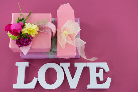 concern: Close-up of gift boxes with flowers and text love against pink background