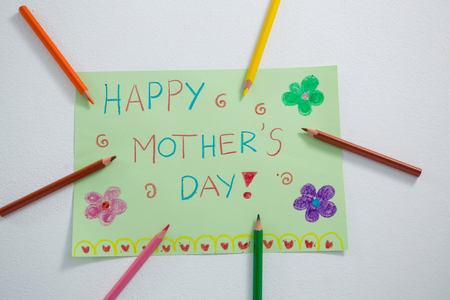 Color pencil arranged around mothers day greetings card on white background
