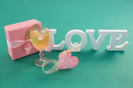 concern: Close-up of gift box and alphabet love on green background Stock Photo