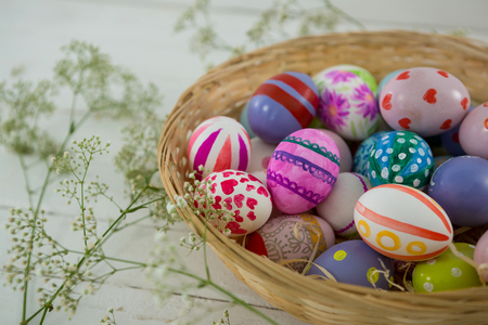 Close-up of basket with painted Easter eggs on wooden background