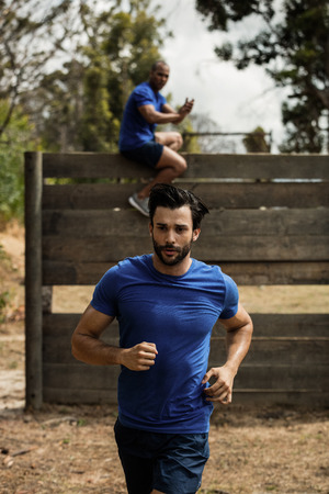 Fit man running during obstacle course in boot camp