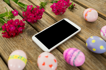 Close-up of painted Easter eggs, flowers and mobile phone on wooden surface