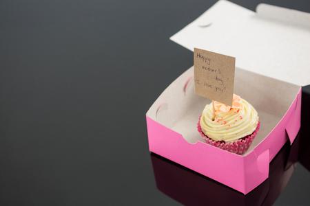 bebes lindos: Close-up de cupcake con feliz tarjeta de día de la madre contra el fondo negro