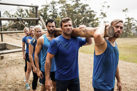 Fit people carrying a heavy wooden log during boot camp training Stock Photo