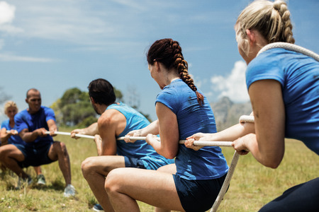 People playing tug of war during obstacle training course in boot camp Reklamní fotografie - 74454661