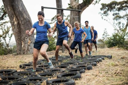 Mensen die banden obstakel opleiding krijgen in boot camp
