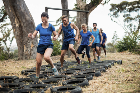People receiving tire obstacle course training in boot camp Stock Photo - 74454690