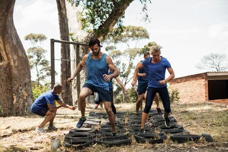 부트 캠프에서 타이어 장애물 코스 훈련을받는 사람들 스톡 콘텐츠