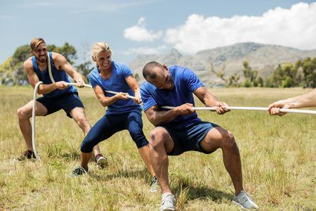 Mensen die een touwtje spelen tijdens een obstakelopleiding in bootkamp