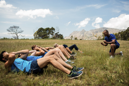 Fit people performing crunches exercise in bootcamp Banco de Imagens