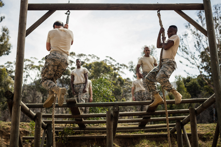 Military soldiers training rope climbing at boot camp