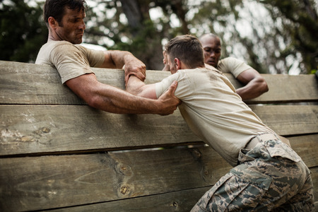 Soldiers helping man to climb wooden wall in boot camp Stockfoto