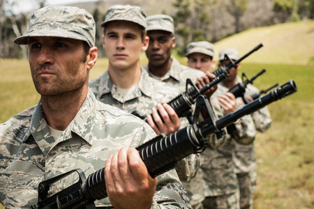Group of military soldiers standing with rifles at boot camp Stock Photo