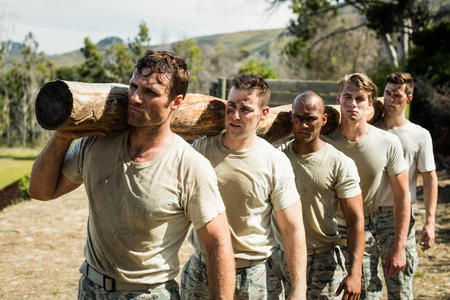 Soldiers carrying a tree log in boot camp Stock Photo