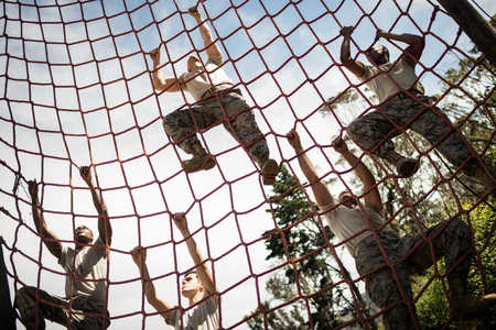 Military soldiers climbing rope during obstacle course in boot camp Stock Photo