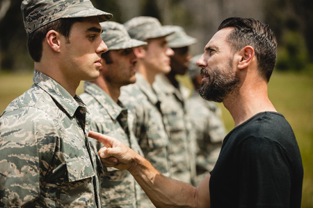 militant: Trainer giving training to military soldier at boot camp