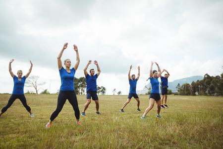 Fit persone che eseguono esercizi di stretching in bootcamp Archivio Fotografico - 74454826