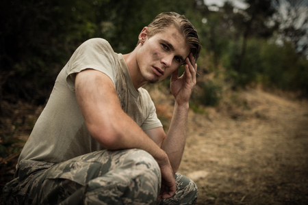 Portrait of soldier with hand on head sitting in boot camp