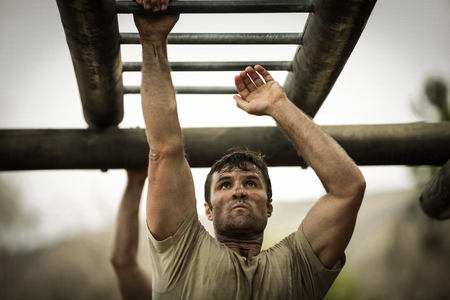 Soldier climbing monkey bars in boot camp Stok Fotoğraf - 74454882