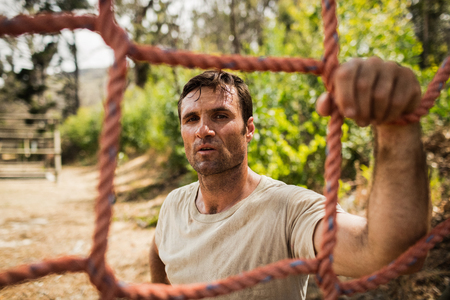 militant: Military soldier standing near fitness trial at boot camp Stock Photo