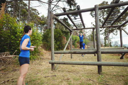 Fit woman climbing monkey bars in bootcamp