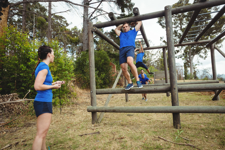 Fit people climbing monkey bars in bootcamp