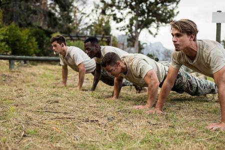 Soldados realizando ejercicio de flexión en el campo de entrenamiento Foto de archivo - 74941339