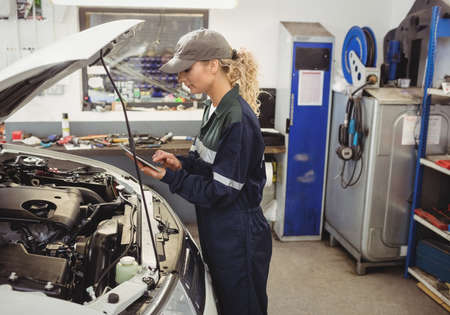 engine bonnet: Female mechanic using digital tablet in repair shop