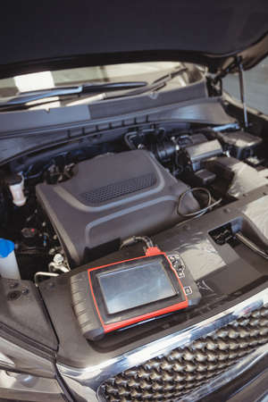 engine bonnet: Car with open bonnet and diagnostic device in repair garage