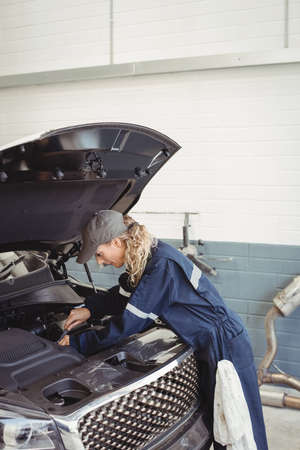 engine bonnet: Female mechanic servicing car at repair garage LANG_EVOIMAGES