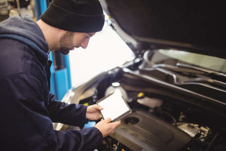 engine bonnet: Mechanic using digital tablet on car in repair garage