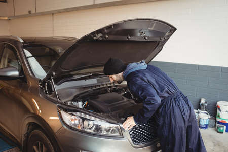 engine bonnet: Mechanic servicing car at repair garage LANG_EVOIMAGES