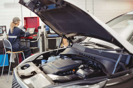 engine bonnet: Female mechanic using laptop in repair garage