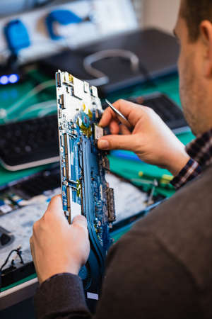 Man repairing laptop in workshop LANG_EVOIMAGES