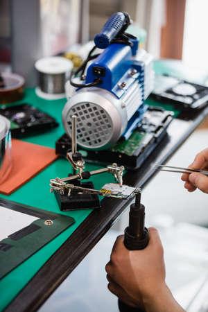 Close-up of man repairing mobile phone in repair centre