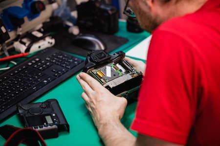 Man repairing digital camera in repair shop