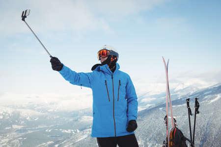 telephone poles: Skier taking selfie on snow covered mountain