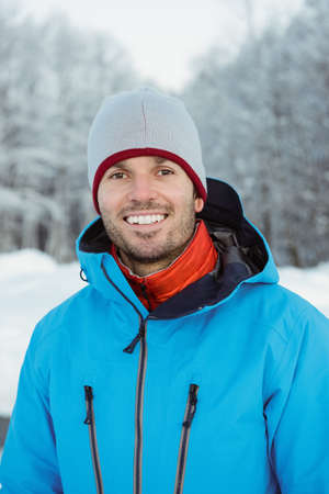 Portrait of smiling man standing on snowy landscape LANG_EVOIMAGES