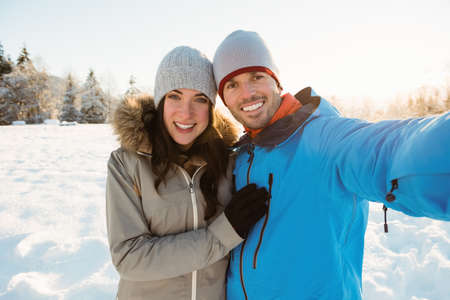 Portrait of happy couple taking a selfie on snowy landscape